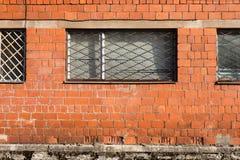 Bakstenen muur met de bars van het metaalvenster stock foto