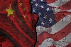 Bakstenen muur met een barst aan verschillende kanten in Chinese en Amerikaanse vlaggen wordt geschilderd die stock fotografie