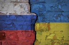 Bakstenen muur met een barst op overkanten in de Oekraïense en Russische vlaggen wordt geschilderd die stock afbeeldingen