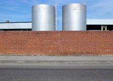 Bakstenen muur met een concrete stoep en een asfaltweg vooraan Tanks voor vloeistof erachter royalty-vrije stock foto