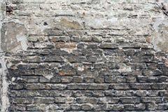 Bakstenen muur met lagen van doorstane gipspleister en teer Stock Afbeeldingen