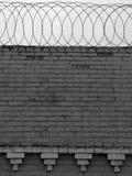 Bakstenen muur met prikkeldraad op bovenkant Stock Foto