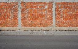 Bakstenen muur met stoep en asfaltweg vooraan Stedelijke achtergrond voor exemplaartekst stock afbeeldingen