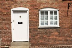 Bakstenen muur met wit deur en venster Royalty-vrije Stock Fotografie