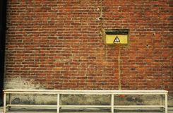 Bakstenen muur met witte bank Stock Afbeeldingen