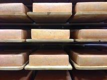 Bakstenen van Emmentaler die op houten planken verouderen Stock Foto