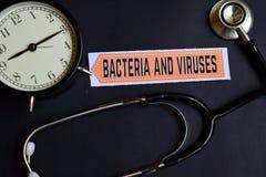 Bakterien und Viren auf dem Papier mit Gesundheitswesen-Konzept-Inspiration Wecker, schwarzes Stethoskop stockbild
