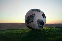 BAKU, ASERBAIDSCHAN - 24. JUNI 2018: Kreatives Konzept Beamter Russland Fußballball mit 2018 Weltcupen Adidas Telstar 18 auf grün Stockbild