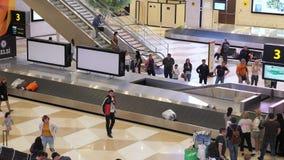 Baku, Aserbaidschan, 20-05-2019: Passagiere warten ihr Gepäck im Flughafenabfertigungsgebäude auf einem Gepäckgurt stock video footage