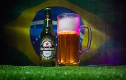 BAKU, AZERBAIJÃO - 21 DE JUNHO DE 2018: Heineken Lager Beer na garrafa com oficial Rússia bola do futebol de 2018 campeonatos do  imagens de stock