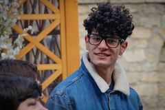 Young attractive Caucasian man with black curly hair and glasses is smiling on a city street royalty free stock photo