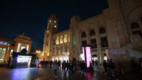 Baku Central Railway Station at night with pedestrians walking. Baku, Azerbaijan - Circa 2019: Wide angle view of people walking near old building of Baku stock video