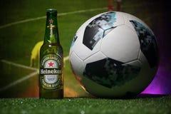BAKU, AZERBAIJAN - 21 DE JUNIO DE 2018: Heineken Lager Beer en botella con el funcionario Rusia bola del fútbol de 2018 mundiales fotos de archivo