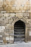 Entrance doorway in an ancient stone wall with stairs leading up. Stock Photography