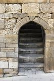 Entrance doorway in an ancient stone wall with stairs leading up. Stock Images
