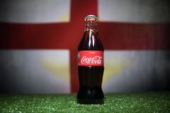 BAKU,AZERBAIJAN - JULY 01, 2018 : Creative concept. Coca-Cola Classic in a glass bottle on grass. Support your country in World cu. P 2018. Selective focus stock photography