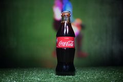 BAKU,AZERBAIJAN - JULY 01, 2018 : Creative concept. Coca-Cola Classic in a glass bottle on grass. Support your country in World cu. P 2018. Selective focus stock photos