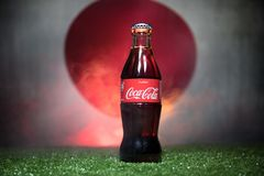 BAKU,AZERBAIJAN - JULY 01, 2018 : Creative concept. Coca-Cola Classic in a glass bottle on grass. Support your country in World cu. P 2018. Selective focus stock photo