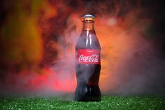 BAKU,AZERBAIJAN - JULY 01, 2018 : Creative concept. Coca-Cola Classic in a glass bottle on grass. Support your country in World cu. P 2018. Selective focus royalty free stock image