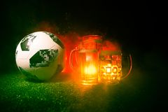 BAKU,AZERBAIJAN - JUNE 23, 2018 : Creative concept. Official Russia 2018 World Cup football ball The Adidas Telstar 18 and Beer gl. Asses on green grass at dark Royalty Free Stock Images