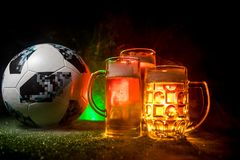 BAKU,AZERBAIJAN - JUNE 23, 2018 : Creative concept. Official Russia 2018 World Cup football ball The Adidas Telstar 18 and Beer gl. Asses on green grass at dark stock photos