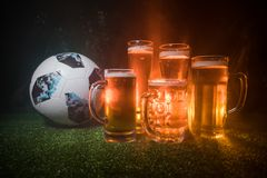 BAKU,AZERBAIJAN - JUNE 23, 2018 : Creative concept. Official Russia 2018 World Cup football ball The Adidas Telstar 18 and Beer gl. Asses on green grass at dark Royalty Free Stock Photography