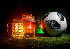 BAKU,AZERBAIJAN - JUNE 23, 2018 : Creative concept. Official Russia 2018 World Cup football ball The Adidas Telstar 18 and Beer gl. Asses on green grass at dark Royalty Free Stock Photo