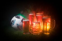 BAKU,AZERBAIJAN - JUNE 23, 2018 : Creative concept. Official Russia 2018 World Cup football ball The Adidas Telstar 18 and Beer gl. Asses on green grass at dark stock image