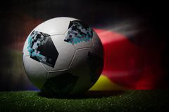 BAKU,AZERBAIJAN - JUNE 21, 2018 : Creative concept. Official Russia 2018 World Cup football ball The Adidas Telstar 18 on dark ton. Ed foggy background with flag Royalty Free Stock Images