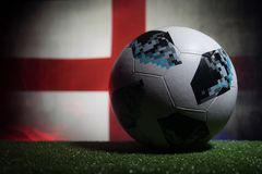 BAKU,AZERBAIJAN - JUNE 21, 2018 : Creative concept. Official Russia 2018 World Cup football ball The Adidas Telstar 18 on dark ton. Ed foggy background with flag stock images