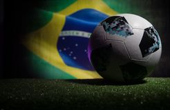 BAKU,AZERBAIJAN - JUNE 21, 2018 : Creative concept. Official Russia 2018 World Cup football ball The Adidas Telstar 18 on dark ton. Ed foggy background with flag Royalty Free Stock Photo