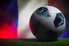 BAKU,AZERBAIJAN - JUNE 21, 2018 : Creative concept. Official Russia 2018 World Cup football ball The Adidas Telstar 18 on dark ton. Ed foggy background with flag Stock Photography