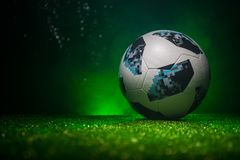 BAKU,AZERBAIJAN - JUNE 21, 2018 : Creative concept. Official Russia 2018 World Cup football ball The Adidas Telstar 18 on green gr. Ass with dark toned foggy royalty free stock image