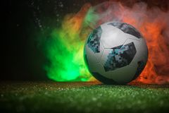 BAKU,AZERBAIJAN - JUNE 21, 2018 : Creative concept. Official Russia 2018 World Cup football ball The Adidas Telstar 18 on green gr. Ass with dark toned foggy stock photo