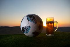 BAKU,AZERBAIJAN - JUNE 24, 2018 : Official Russia 2018 World Cup football ball The Adidas Telstar 18 and glass of beer on at sunse. T background. Defeat football royalty free stock photography