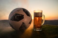 BAKU,AZERBAIJAN - JUNE 24, 2018 : Official Russia 2018 World Cup football ball The Adidas Telstar 18 and glass of beer on at sunse. T background. Defeat football stock image