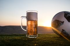 BAKU,AZERBAIJAN - JUNE 24, 2018 : Official Russia 2018 World Cup football ball The Adidas Telstar 18 and glass of beer on at sunse. T background. Defeat football Stock Photo