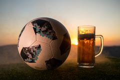 BAKU,AZERBAIJAN - JUNE 24, 2018 : Official Russia 2018 World Cup football ball The Adidas Telstar 18 and glass of beer on at sunse. T background. Defeat football Royalty Free Stock Image