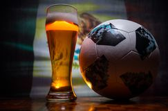 BAKU,AZERBAIJAN - JUNE 21, 2018 : Official Russia 2018 World Cup football ball The Adidas Telstar 18 and single beer glass with bl. Urred flag on background stock images