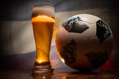 BAKU,AZERBAIJAN - JUNE 21, 2018 : Official Russia 2018 World Cup football ball The Adidas Telstar 18 and single beer glass with bl. Urred flag on background Stock Photo