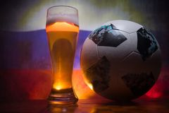 BAKU,AZERBAIJAN - JUNE 21, 2018 : Official Russia 2018 World Cup football ball The Adidas Telstar 18 and single beer glass with bl. Urred flag on background Royalty Free Stock Photography