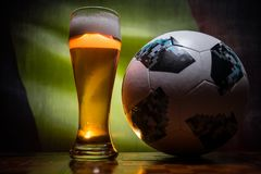 BAKU,AZERBAIJAN - JUNE 21, 2018 : Official Russia 2018 World Cup football ball The Adidas Telstar 18 and single beer glass with bl. Urred flag on background stock image