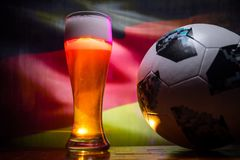 BAKU,AZERBAIJAN - JUNE 21, 2018 : Official Russia 2018 World Cup football ball The Adidas Telstar 18 and single beer glass with bl. Urred flag on background Stock Photos