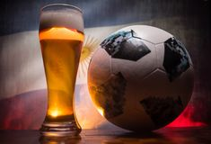 BAKU,AZERBAIJAN - JUNE 21, 2018 : Official Russia 2018 World Cup football ball The Adidas Telstar 18 and single beer glass with bl. Urred flag on background Royalty Free Stock Photo