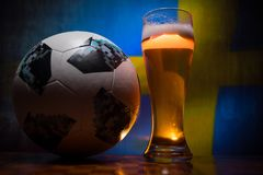 BAKU,AZERBAIJAN - JUNE 21, 2018 : Official Russia 2018 World Cup football ball The Adidas Telstar 18 and single beer glass with bl. Urred flag on background Stock Photography