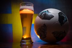 BAKU,AZERBAIJAN - JUNE 21, 2018 : Official Russia 2018 World Cup football ball The Adidas Telstar 18 and single beer glass with bl. Urred flag on background Royalty Free Stock Image