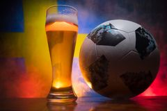 BAKU,AZERBAIJAN - JUNE 21, 2018 : Official Russia 2018 World Cup football ball The Adidas Telstar 18 and single beer glass with bl. Urred flag on background royalty free stock photos