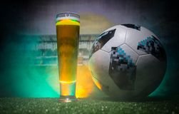 BAKU,AZERBAIJAN - JUNE 23, 2018 : Official Russia 2018 World Cup football ball The Adidas Telstar 18 and single beer glass on gras. S at dark toned foggy Stock Photography
