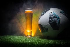 BAKU,AZERBAIJAN - JUNE 23, 2018 : Official Russia 2018 World Cup football ball The Adidas Telstar 18 and single beer glass on gras. S at dark toned foggy Royalty Free Stock Images