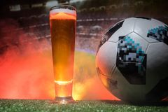BAKU,AZERBAIJAN - JUNE 23, 2018 : Official Russia 2018 World Cup football ball The Adidas Telstar 18 and single beer glass on gras. S at dark toned foggy Stock Photos